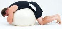 Лег по корем върху швейцарска топка